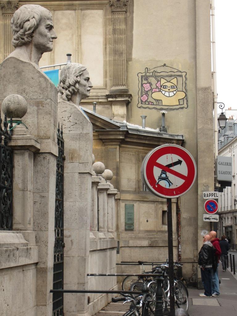 a paris street sign graffiti with eiffel tower