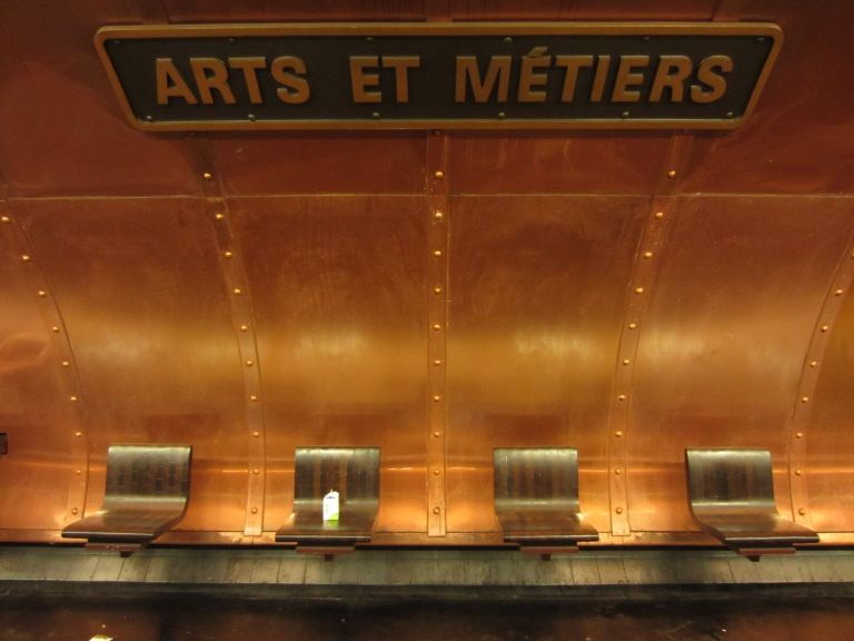 wooden chairs and a metal wall in a paris station