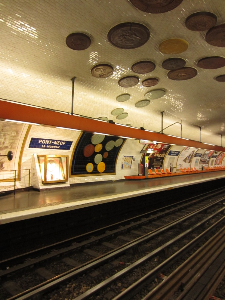 coin sculptures on the ceiling of a paris metro