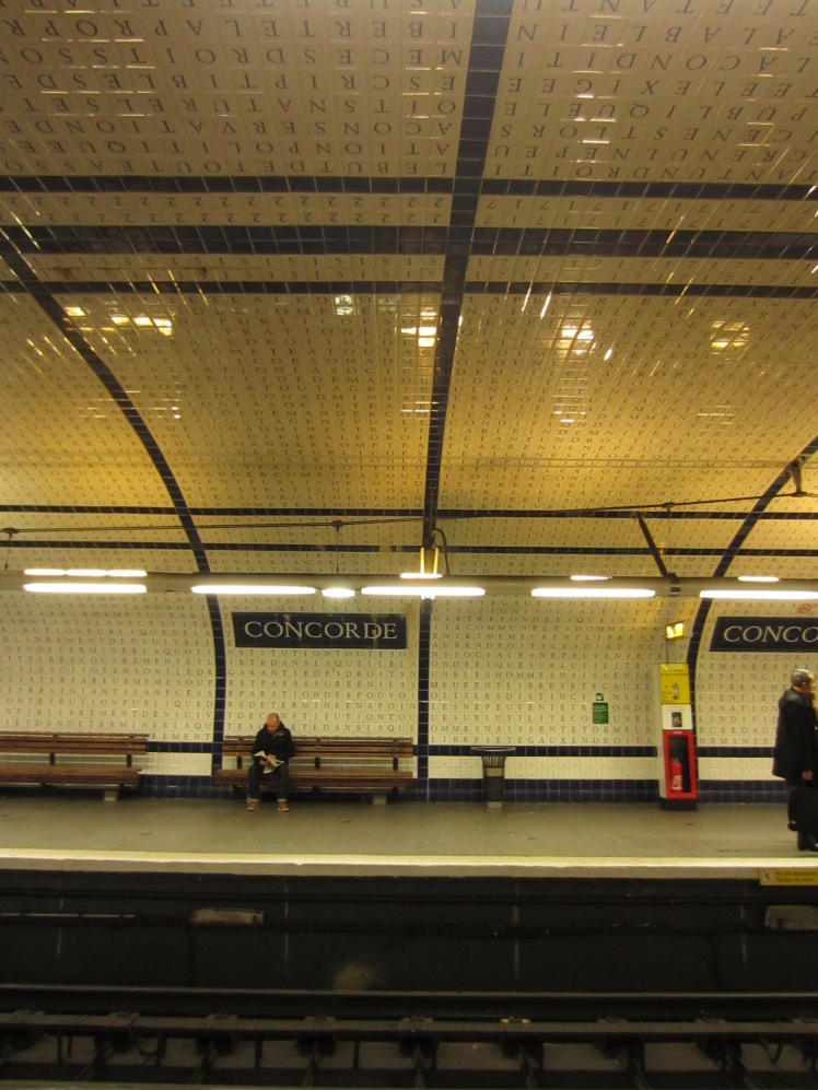 paris metro station with letters on the white tiles