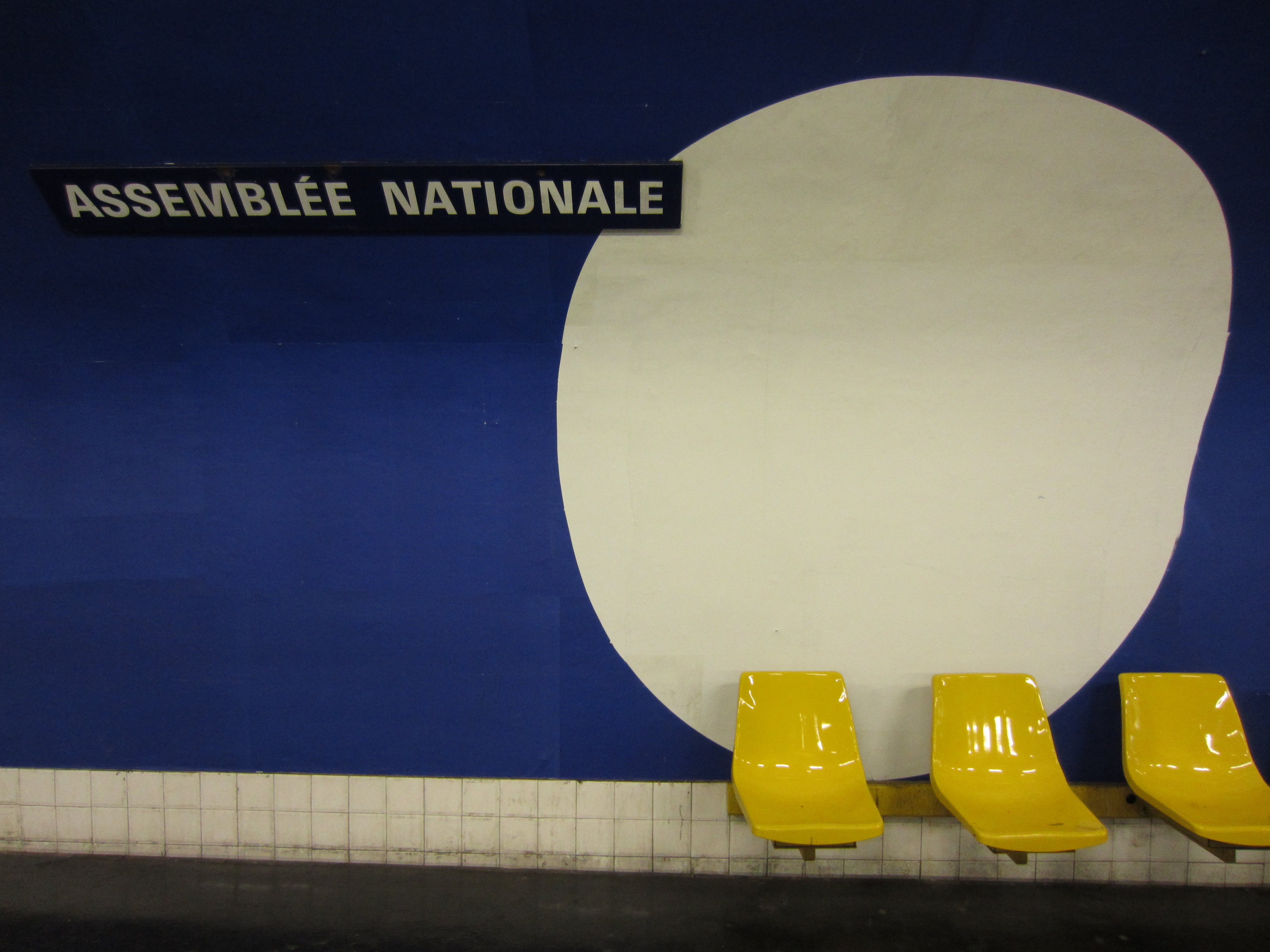 a large white circle painted against a blue background in the paris metro