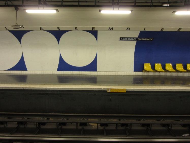white and blue public art on a paris metro station