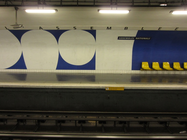 white and blue public art on a paris metro station