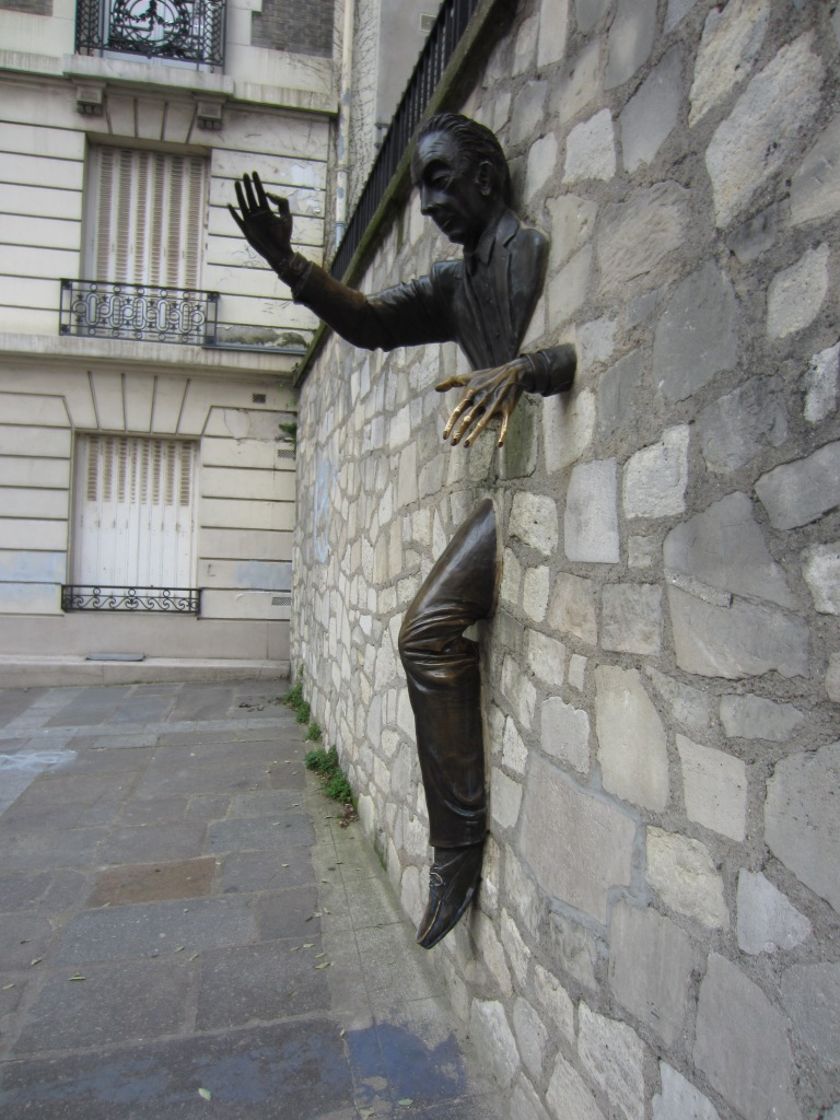 statue of a man walking through a wall