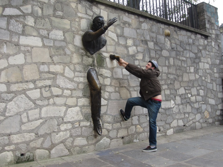 statue of a man walking through a wall with a man interacting