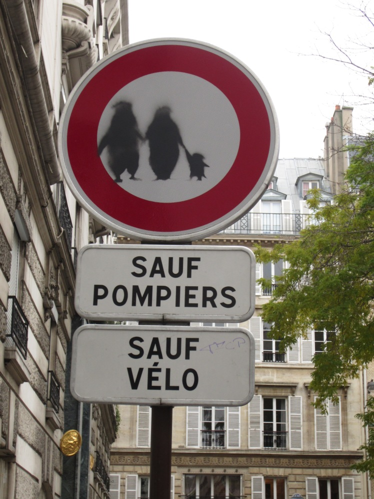 a modified street sign with penguins