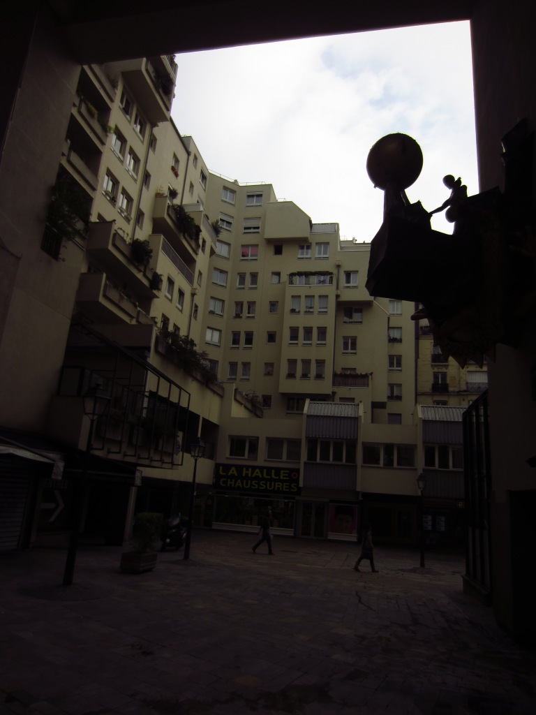 backstreet in paris with a sculpture on the wall