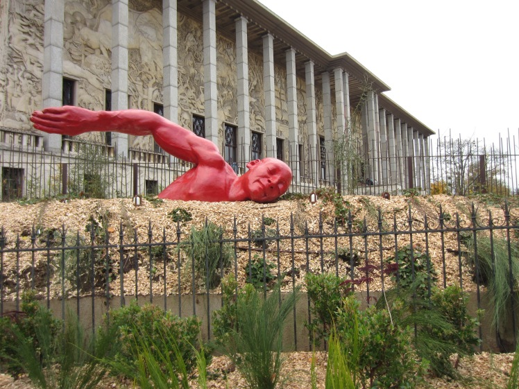 A public art display of a red man swimming in a garden