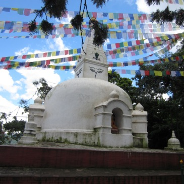 a white stupa in Nepal with colorful buddhist flags
