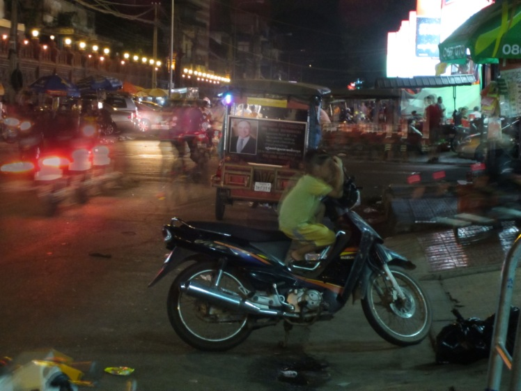 The streets of Phnom Penh, where kids babysit motorcycles