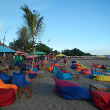 A balinese beach with colored bean bags and umbrellas
