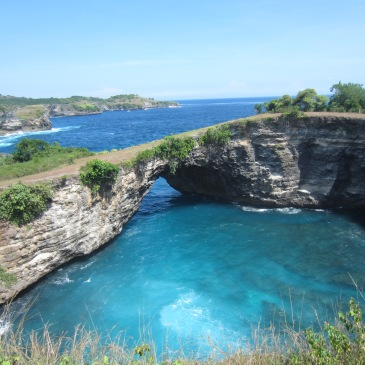 a natural rock arch spans a blue lake