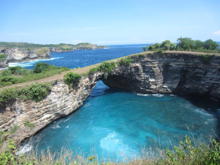a natural rock arch spans a blue lake