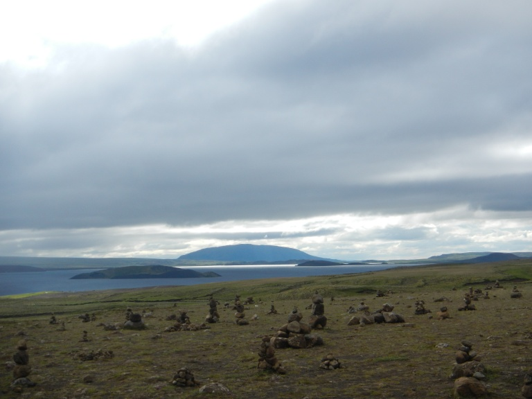 a field of rocks and a distant lake in iceland