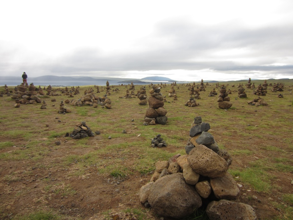 a field in iceland with piles of stacked rocks