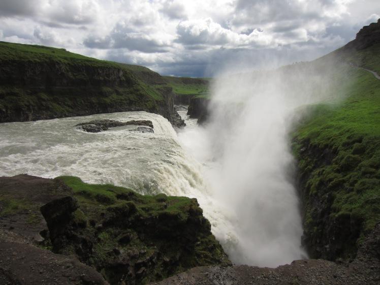 an icelandic waterfall sprays water up