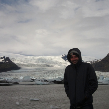 a man in a jacket poses in front of an icy glacier