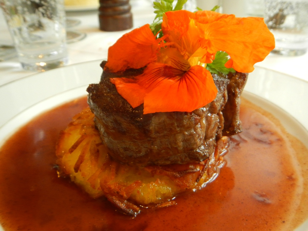 A delicious steak and potato with gravy and a flower for garnish