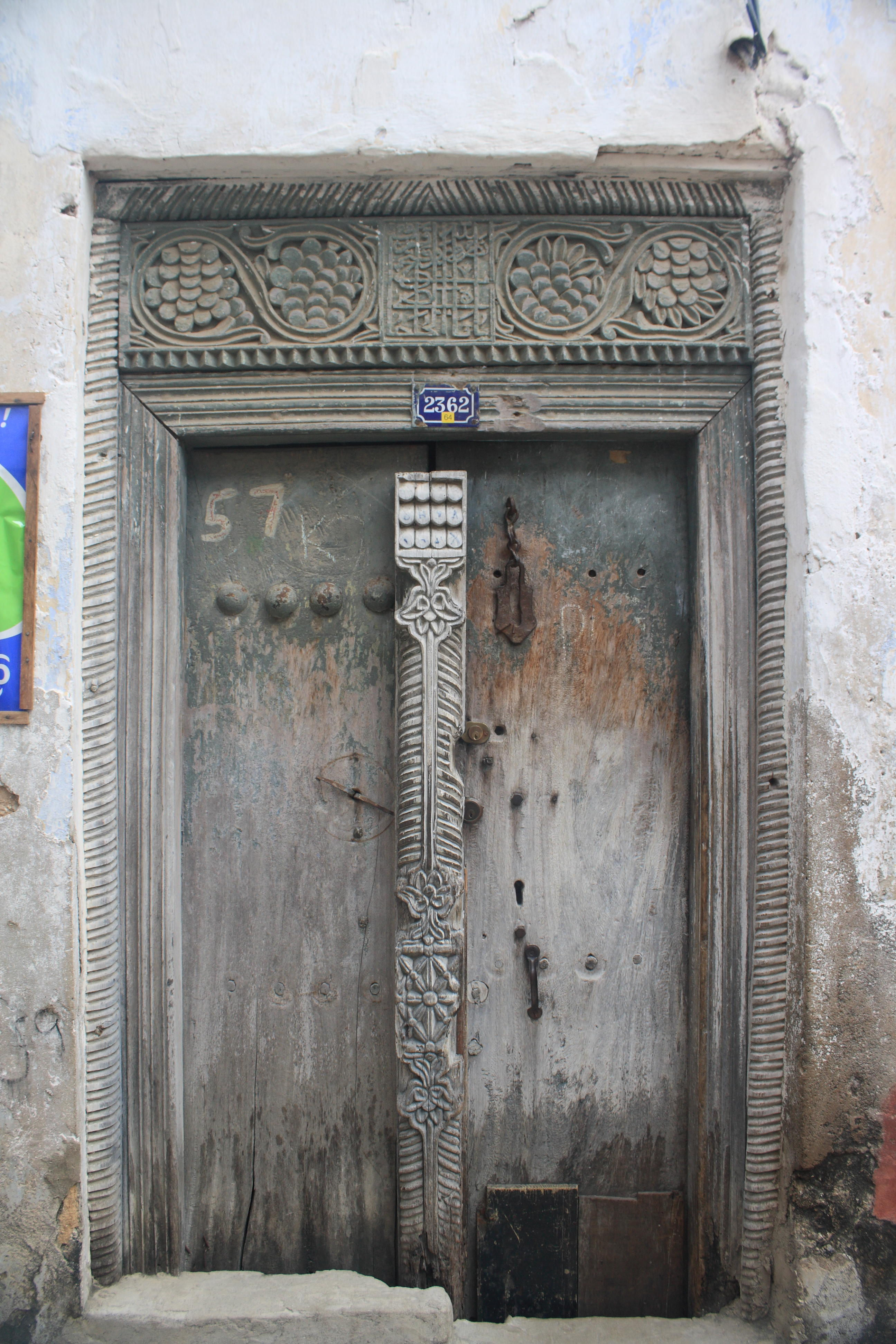 A warped zanzibar door with intricate beam carvings
