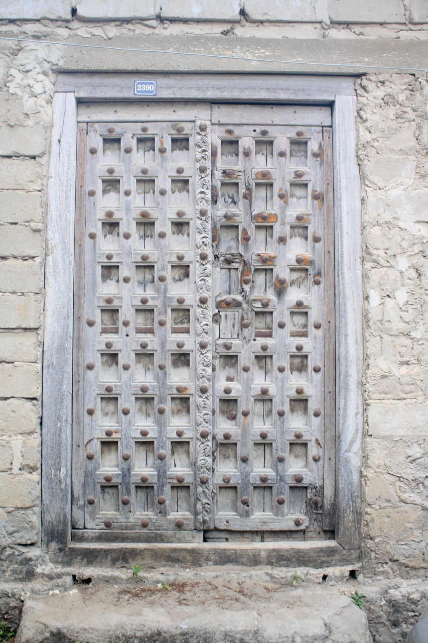 An white Indian style Zanzibar door with small windows and studs