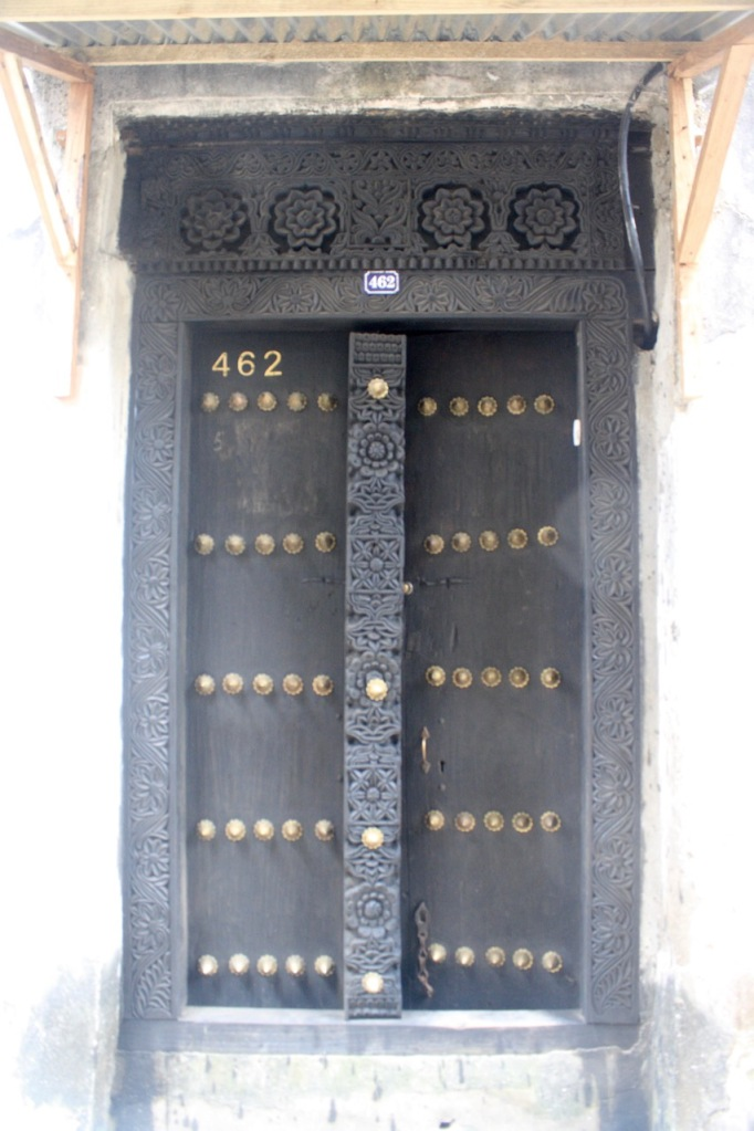 A door in Stone Town with black wood and flowers