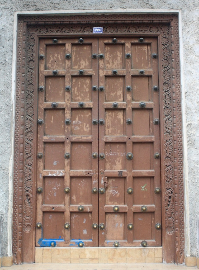An old wooden door in Zanzibar with wood panels and metal studs