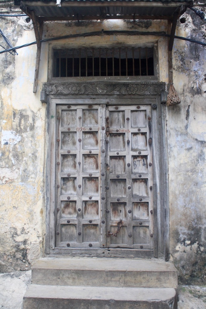 A Zanzibar door with metal bars and faded wood