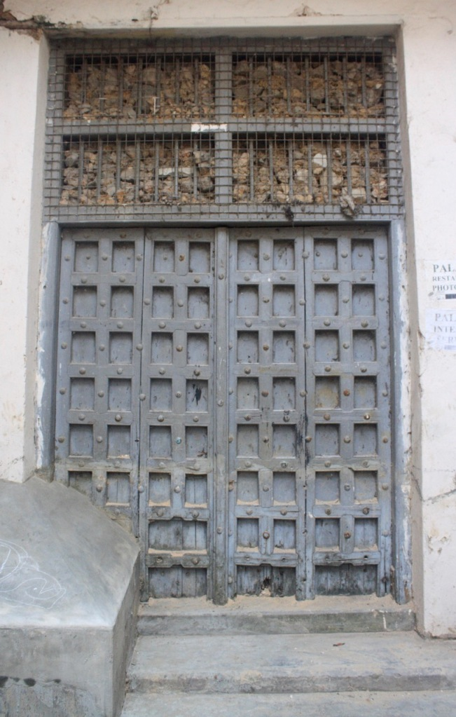 A rock pile in a metal grate above a Zanzibar door