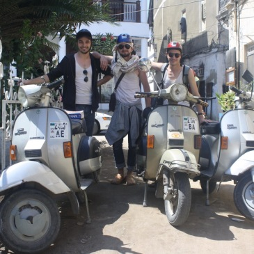 Three men pose with scooters in a zanzibar street