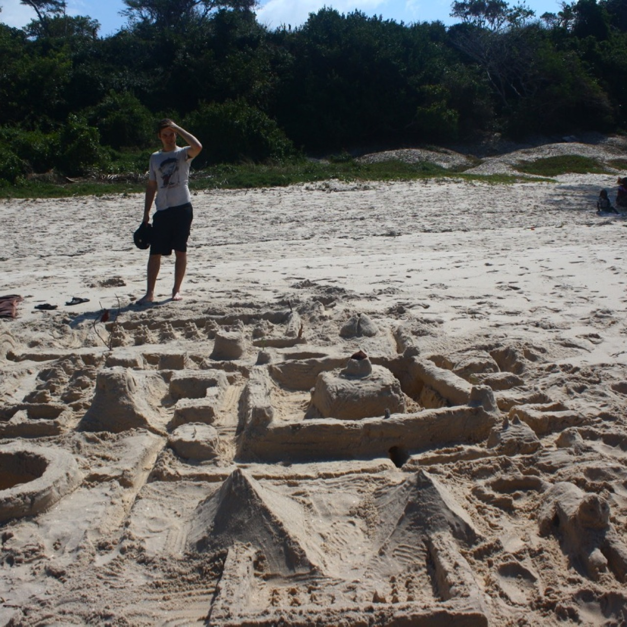A man looks at a large intricate sandcastle