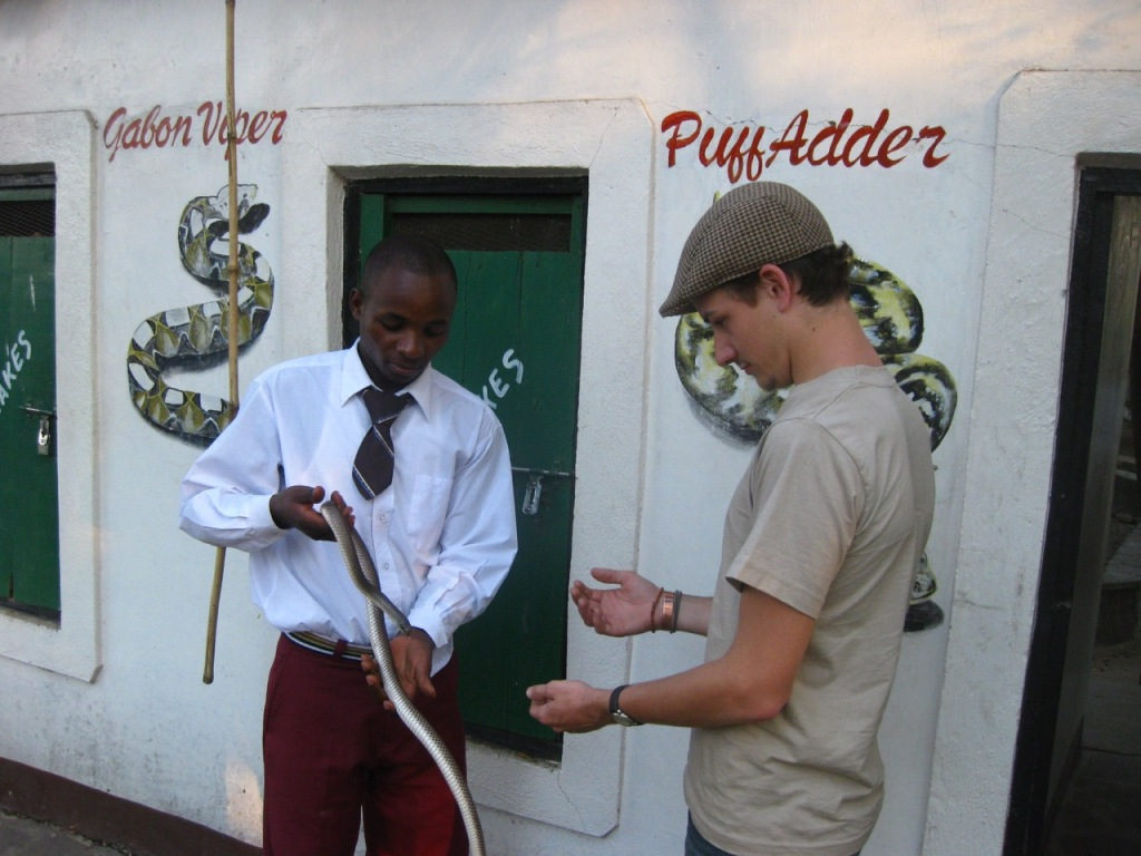 A snake park employee shows a snake to a visitor