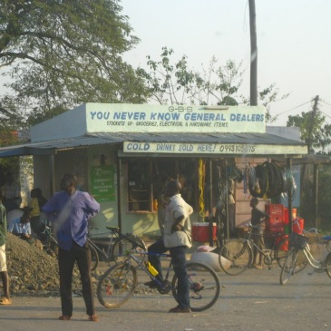 A malawi general store with a group of locals and a bicycle