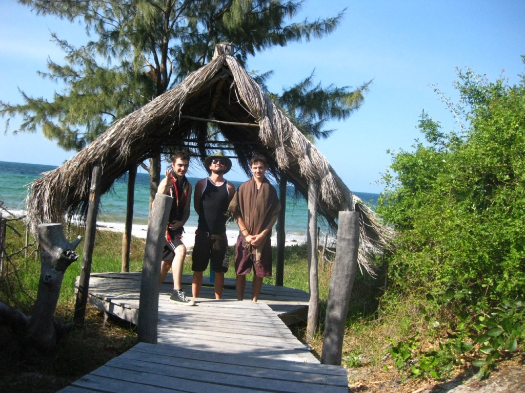 Three people under a thatch shelter on inhassoro beach
