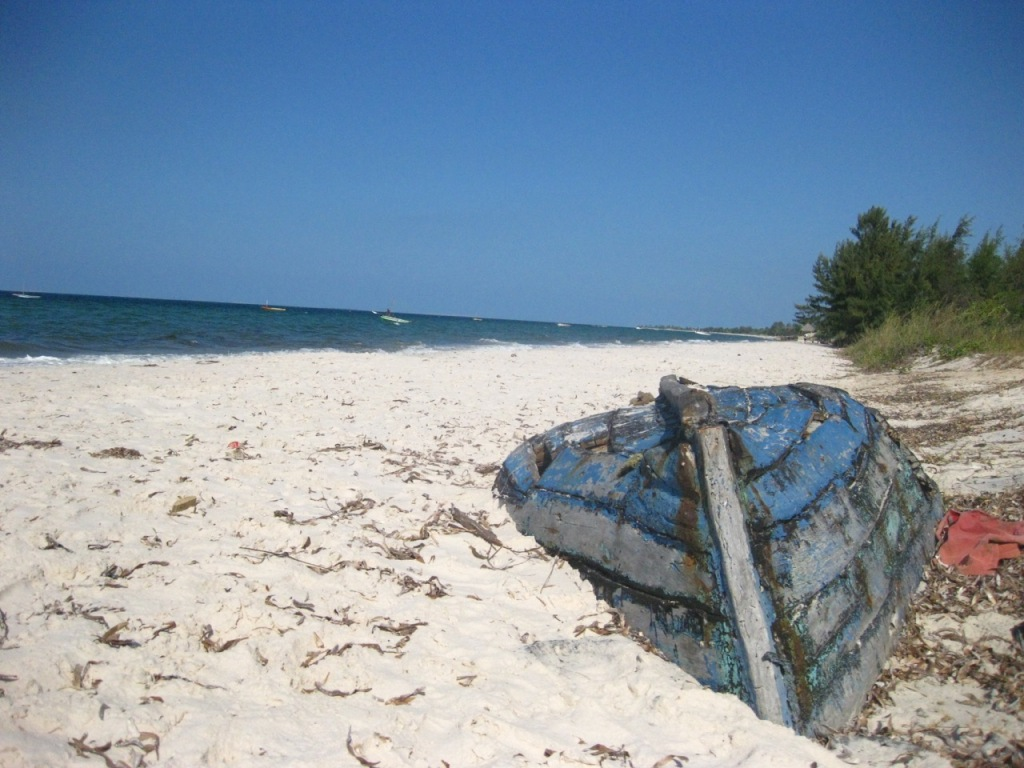 An old wooden boat upside down on inhassoro beach