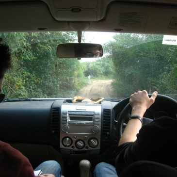 two people drive on a dirt road